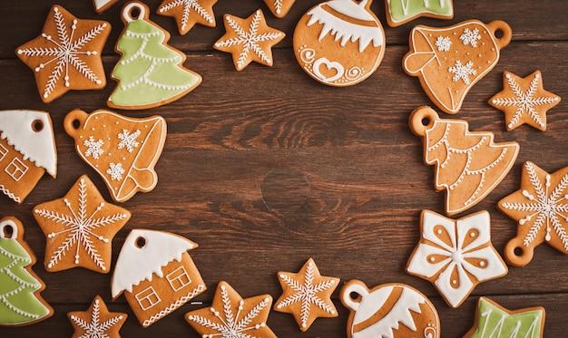 De feestelijke koekjes van de kerstmispeperkoek in de vorm van een ster liggen op een houten donkere bruine achtergrond. Premium Foto