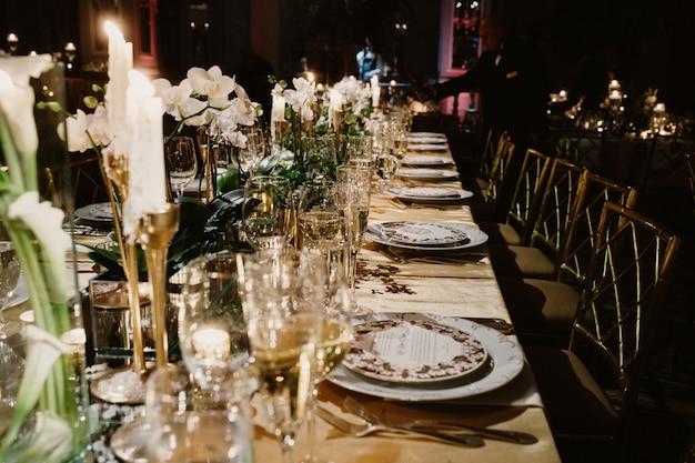 De feestelijke tafel in het restaurant is versierd met kaarsen en bloemen Gratis Foto