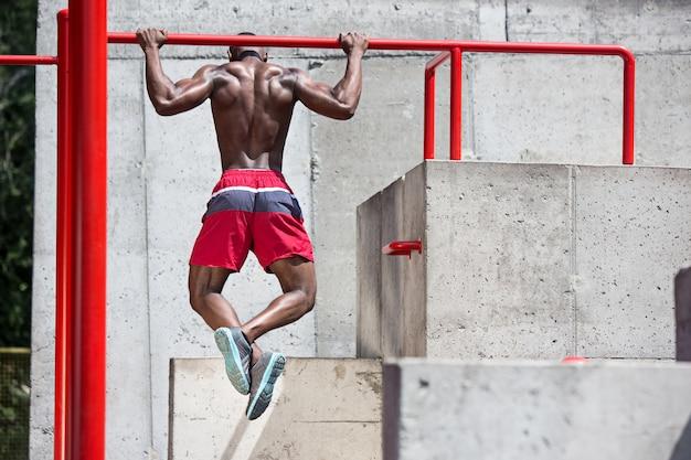 De fitte atleet die oefeningen doet. afro of afro-amerikaanse man buiten in de stad. trek sportoefeningen uit. Gratis Foto
