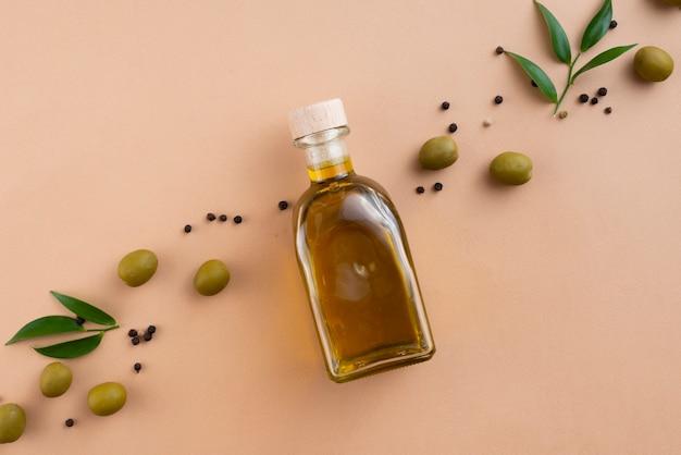 De fles van de olijvenolie met gespreide olijven en bladeren daarna Gratis Foto