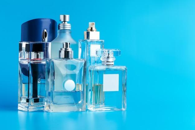 De fles van het mensenparfum op blauwe dichte omhooggaand Premium Foto
