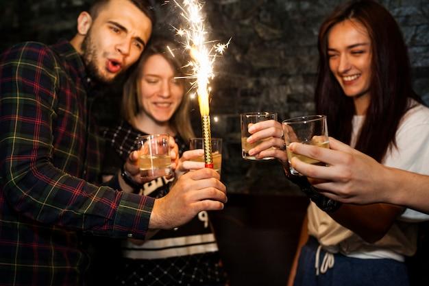 De fonkelingskaars die van de mensenholding van dranken met vrienden houden Gratis Foto