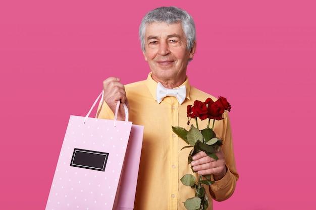 De foto van de aantrekkelijke rijpe mens met prettige gelaatsuitdrukking, gekleed in geel overhemd met witte vlinderdas, draagt roze zak met heden en rozen, wil vrouw met huwelijksverjaardag gelukwensen. Gratis Foto