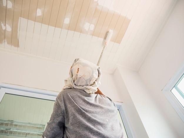 De foto van de gedeeltelijke nadruk van een mens schildert plafond gebruikend rolborstel Gratis Foto