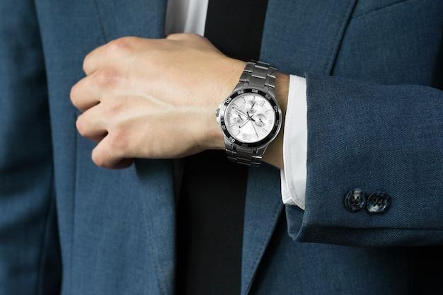 De foto van de zakenman in een pak. een hand met uren Premium Foto