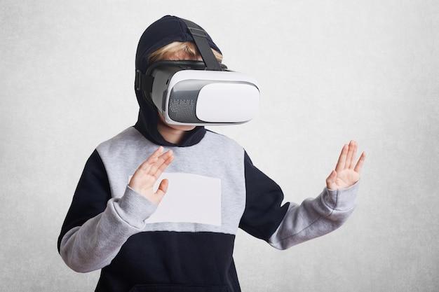 De foto van een klein kind draagt een virtual reality-bril Gratis Foto