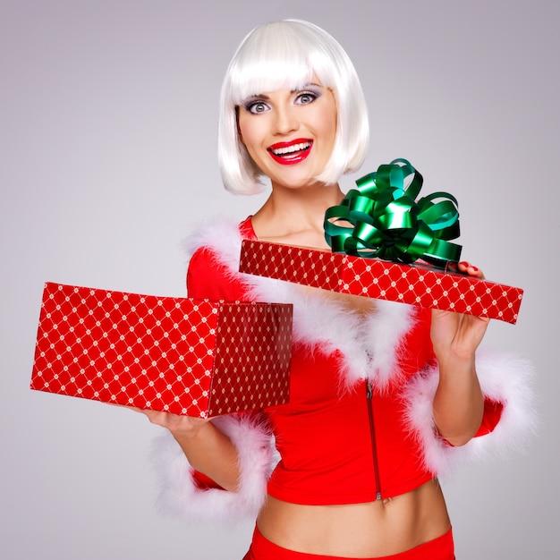 De foto van mooi sneeuwmeisje houdt de giftdoos van het kerstmisnieuwjaar Gratis Foto
