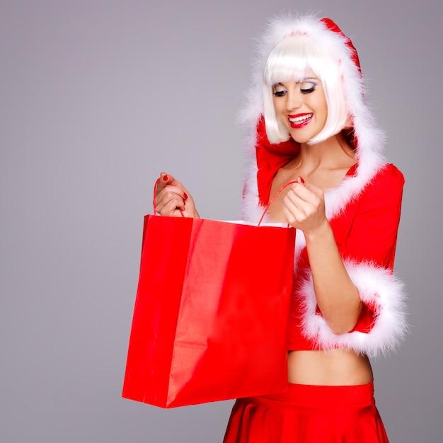 De foto van mooi sneeuwmeisje houdt het rode winkelen slecht Gratis Foto