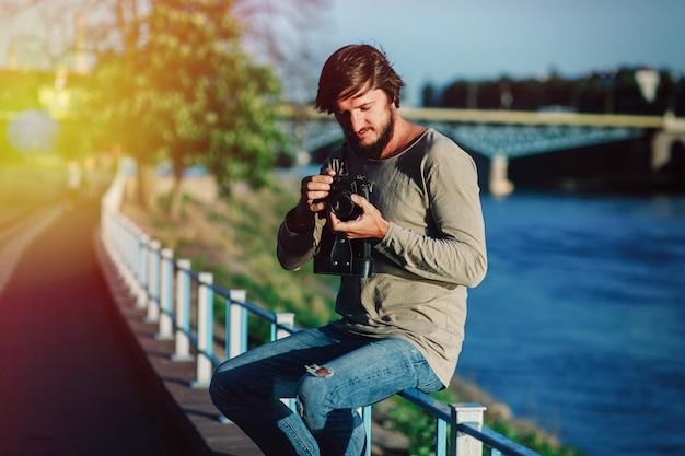 De fotograaf van de hipstermens maakt landschapsfotografie met retro oud middelgroot formaat van de filmcamera Premium Foto