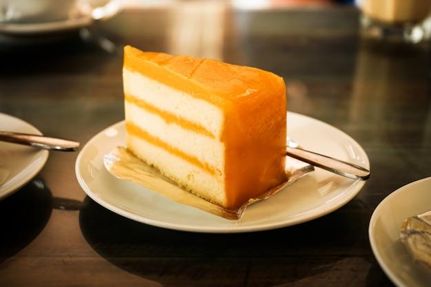 De fruit oranje cake op witte plaat dressert eet met koffie ontspant tijd in resturant Premium Foto