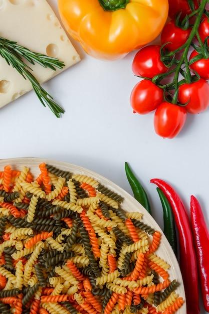 De fusillideegwaren met tomaten, peper, installatie op kaas in een plaat op witte vlakke lijst, leggen. Gratis Foto