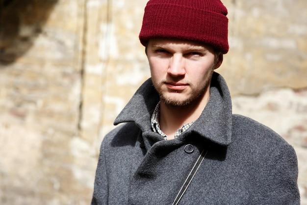 De gebaarde jonge mens in rode hoed en grijze laag stelt vóór beige muur Gratis Foto