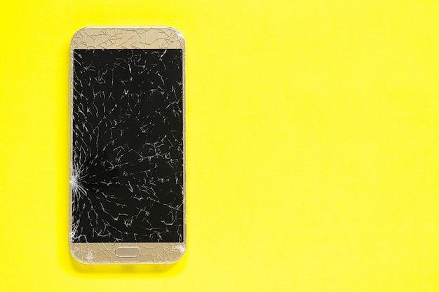 De gebroken barstencel mobiele telefoon op gele achtergrond Premium Foto