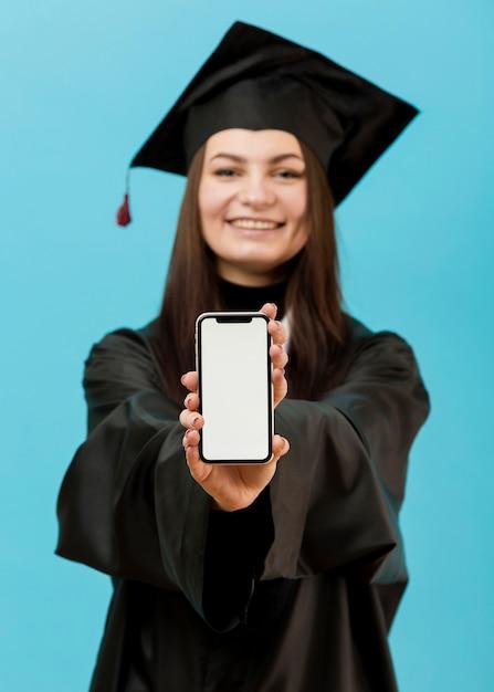 De gediplomeerde student van smiley met telefoon Gratis Foto