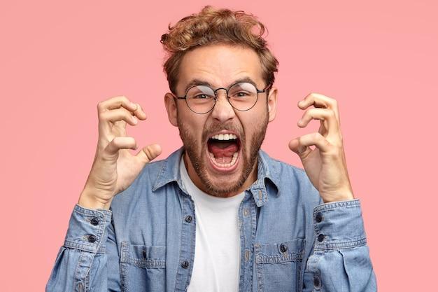 De geërgerde man van peevish gebaart boos, drukt negatieve emoties uit, houdt de mond wijd open Gratis Foto