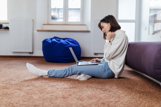 De geïnteresseerde studentenvrouw werkt aan laptop computerzitting op de vloer thuis in casual gekleed dagtijd Gratis Foto