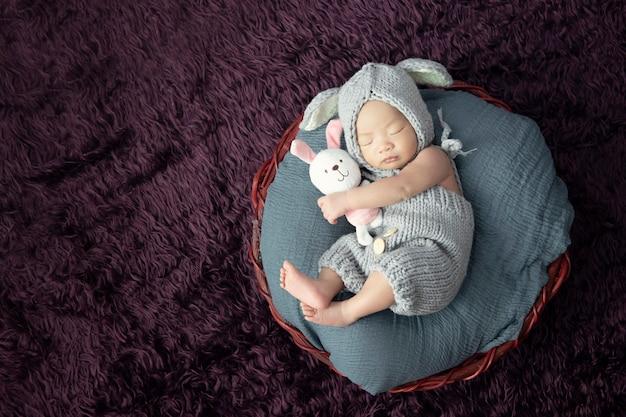 De gelukkige aanbiddelijke slaap van het babymeisje met pop in klein bed. Premium Foto