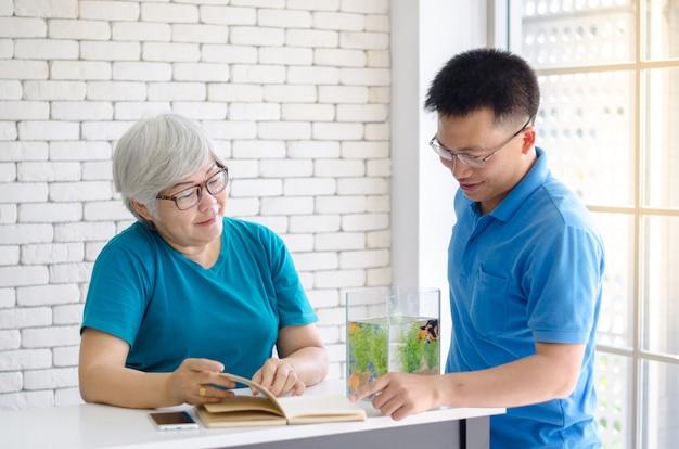 De gelukkige aziatische hogere vrouw die een boek leest en raadpleegt het spreken met haar zoon en goede tijd Premium Foto