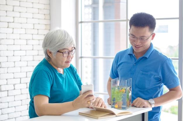 De gelukkige aziatische hogere vrouw die een boek leest en raadpleegt het spreken met haar zoon Premium Foto