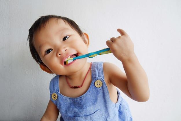 De gelukkige aziatische praktijk die van het babymeisje haar tanden borstelt. Premium Foto