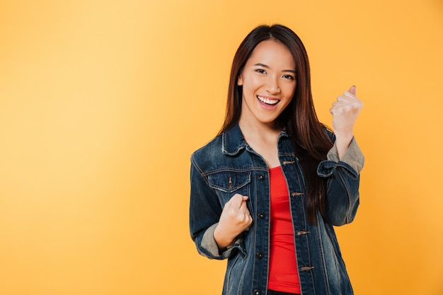 De gelukkige aziatische vrouw in jasje verheugt zich en bekijkend camera Gratis Foto