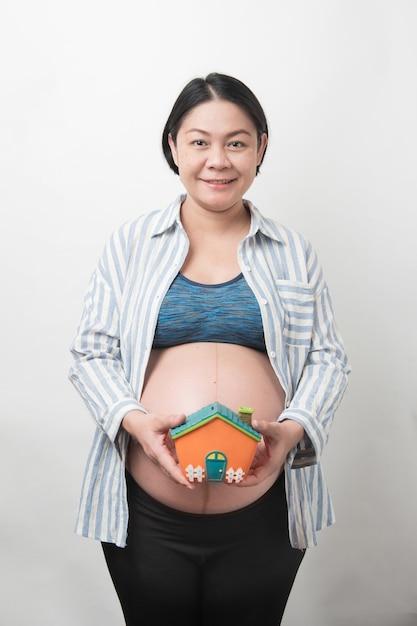 De gelukkige aziatische zwangere moeder in de holdings van het glimlachgezicht en toont het huis-vormige geïsoleerde spaarvarken, zwangerschapsconcept Premium Foto