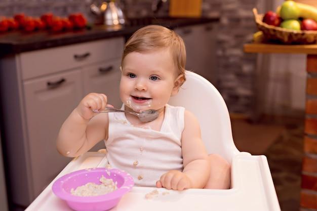 De gelukkige baby eet melkpap met een lepel Premium Foto