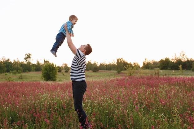 De gelukkige blije vader die pret heeft werpt omhoog in het luchtkind. zonlicht op de zonsondergang Gratis Foto
