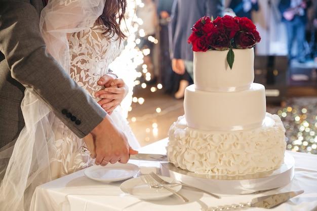 De gelukkige bruid en de bruidegom snijden een huwelijkscake Gratis Foto