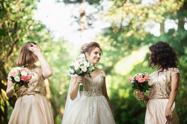 De gelukkige bruid met bruidsmeisje houdt boeketten en heeft buiten plezier. achtergrond van de natuur Premium Foto