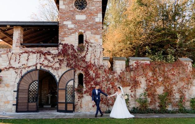 De gelukkige bruidegom en de bruid houden samen handen en lopen voor oude steen voortbouwend op de warme de herfstdag Gratis Foto