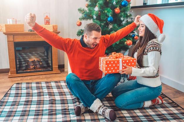De gelukkige en opgewekte mens zit op deken met gekruiste vingers en rekt handen uit Premium Foto