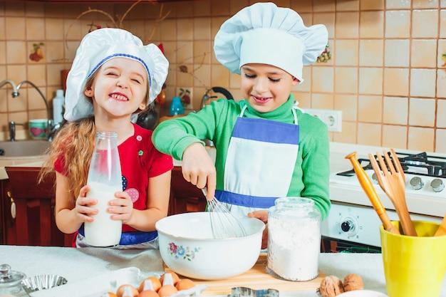 De gelukkige familie grappige jonge geitjes bereiden deeg voor, bakken koekjes in keuken Gratis Foto