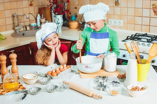 De gelukkige familie grappige jonge geitjes bereiden het deeg voor, bakken koekjes in de keuken Gratis Foto