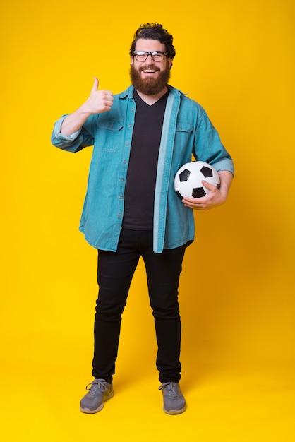 De gelukkige gebaarde mens toont als of duim op gebaar terwijl het houden van een voetbalbal Premium Foto