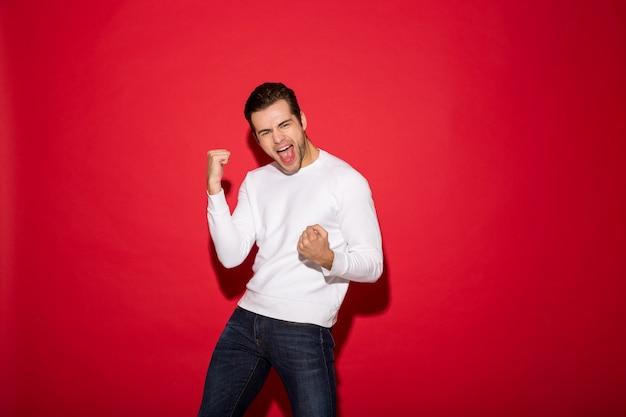 De gelukkige gillende mens in sweater verheugt zich en kijkend Gratis Foto