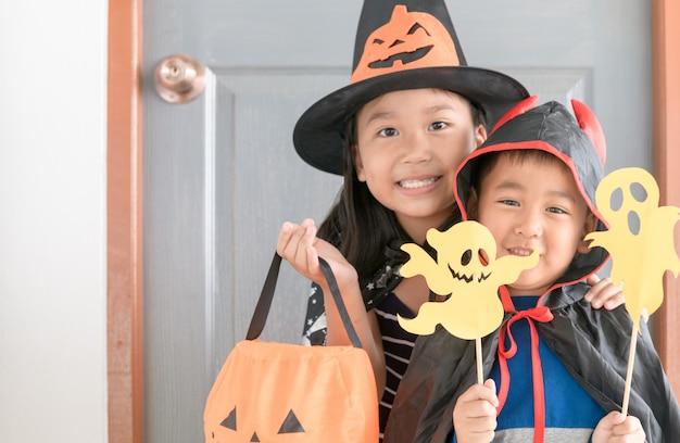 De gelukkige glimlach van de jongensduivel en schattige kleine heks Premium Foto
