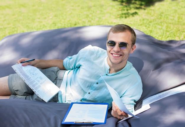 De gelukkige glimlachende jonge student bestudeert in openlucht, leggend op een groot kussen. Premium Foto