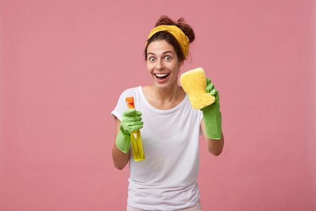 De gelukkige huisvrouw kleedde zich in vrijetijdskleding die de spons en het afwasmiddel houdt die huis gaan schoonmaken met goed geïsoleerd humeur Gratis Foto