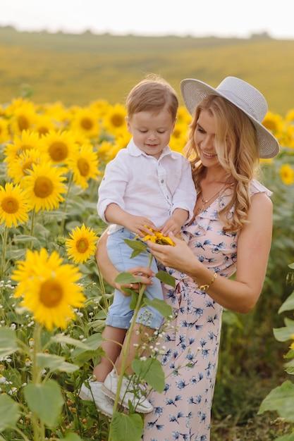 De gelukkige jonge familie, de moedervader en de zoon, glimlachen, houden en koesteren op het zonnebloemgebied Gratis Foto