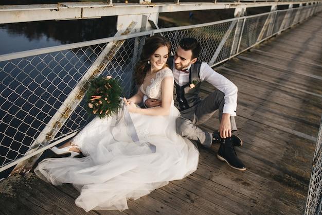 De gelukkige jonge glimlachende bruid en de bruidegom zitten op de hangbrug. zonnige trouwfoto's op een interessante plek Premium Foto
