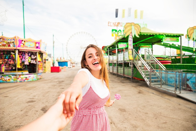 De gelukkige jonge hand van de vrouwenholding van haar vriend bij pretpark Gratis Foto