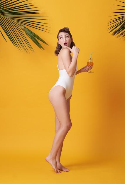 De gelukkige jonge mooie vrouw kleedde zich in badmode houdend een sinaasappel Premium Foto