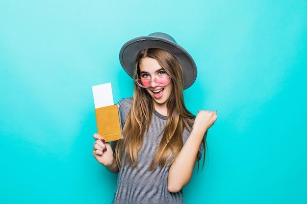De gelukkige jonge tienerdame houdt haar paspoortdocumenten met kaartje in haar handen die op groene studiomuur worden geïsoleerd Gratis Foto