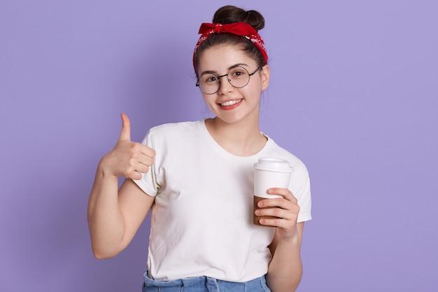 De gelukkige jonge vrouw die duim toont en houdt neemt koffie weg, kijkt glimlachend rechtstreeks in camera, die vrijetijdskleding en rode haarband draagt Gratis Foto