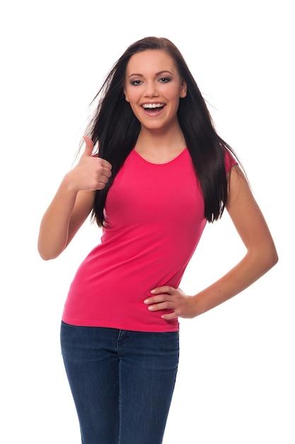 De gelukkige jonge vrouw die duimen toont ondertekent omhoog Gratis Foto