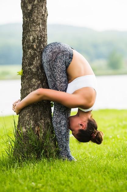 De gelukkige jonge vrouw die zich in yoga bevindt stelt op het gras in het park Gratis Foto