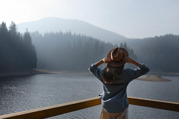De gelukkige jonge vrouw in hoed geniet van meermening in bergen. ontspannende momenten in het bos. achteraanzicht van stijlvolle meisje geniet van de frisheid buiten. vrijheid, mensen, levensstijl, reizen en vakantie Premium Foto