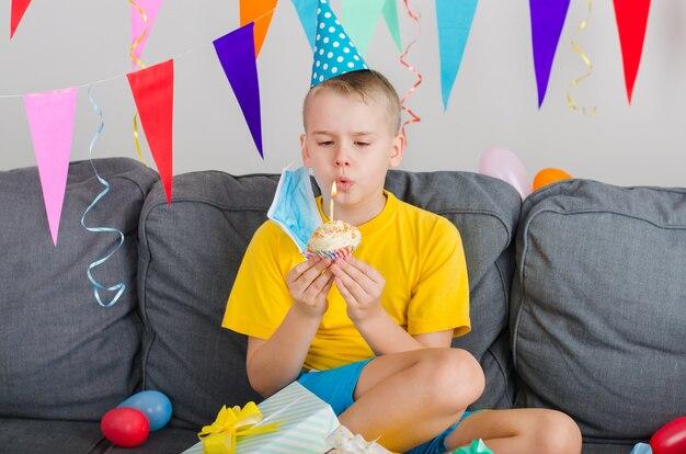 De gelukkige jongen zette zijn gezichtsmasker af, hield vakantie cupcake en blaast kaars uit Premium Foto