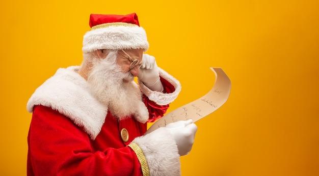 De gelukkige kerstman die uitstekend document op geel houdt Premium Foto